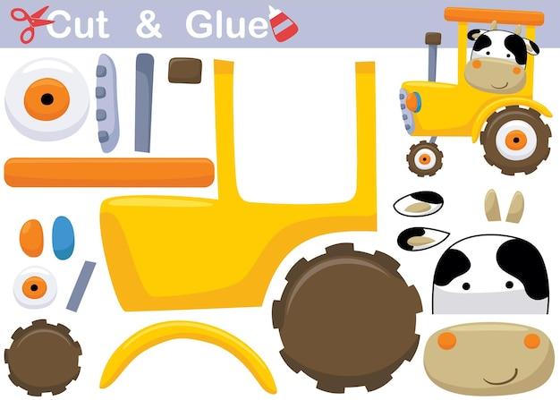 Śmieszna krowa na żółtym ciągniku. papierowa gra edukacyjna dla dzieci. wycięcie i klejenie