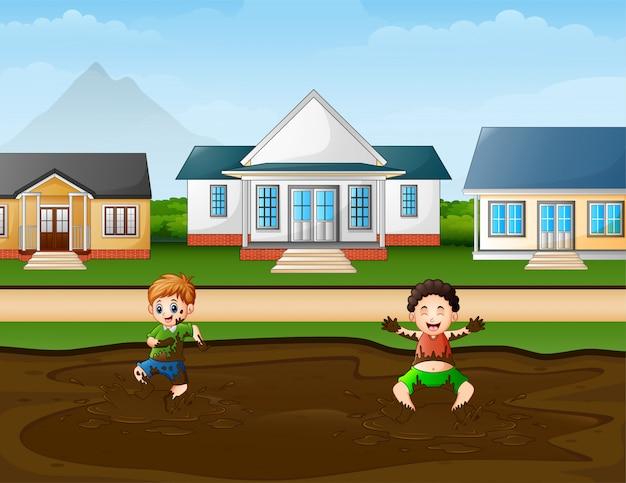 Śmieszne dzieci bawiące się w kałuży błota na wsi