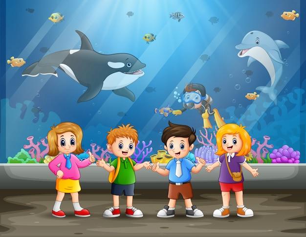 Śmieszni dzieci w wieku szkolnym patrzeje ryba w akwarium