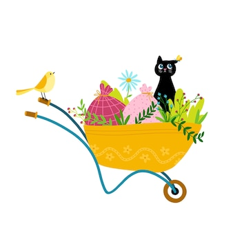 Śmieszny czarny kot z motylem na uchu na taczce ogrodowej z roślinami i torbami.