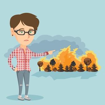 Smutna kobieta wskazuje na pożar.
