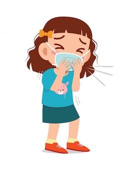 Smutna śliczna mała dziewczynka kicha z powodu grypy