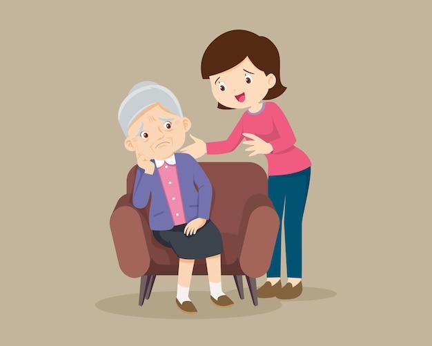 Smutna starsza kobieta znudzona, smutna starsza kobieta siedząca i kobieta pocieszająca ją zdenerwowana