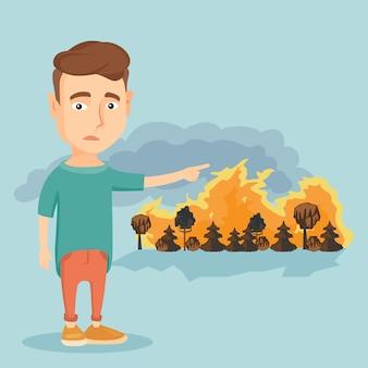 Smutny człowiek wskazujący na pożar.