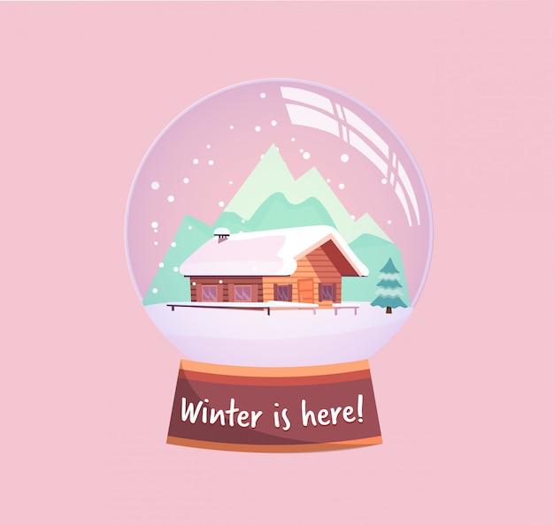 Śnieżna kula ziemska z małym domkiem, górami i jodłą