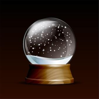 Śnieżna kula ziemska ze spadającymi płatkami śniegu. realistyczna przezroczysta szklana kula na drewnianym cokole. magiczna szklana kula na ciemnym tle.