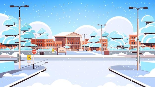 Śnieżny budynek szkolny pusty frontowy dziedziniec ze śniegiem zimowym pejzażem miejskim w tle