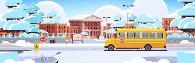 Śnieżny budynek szkolny pusty podwórko z drzewami droga i autobus szkolnyzimowy pejzaż miejski w tle