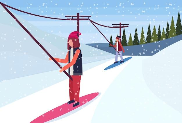 Snowboardziści zjeżdżają z góry za pomocą wyciągu narciarskiego