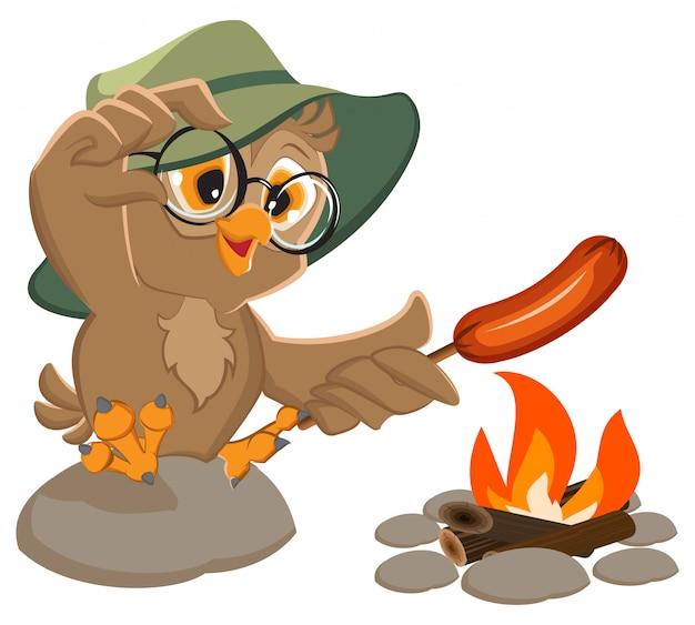 Sowa piknikowa harcerza smaży kiełbasę w ogniu