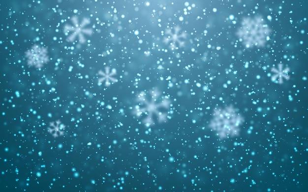 Spadające płatki śniegu na niebieskim tle