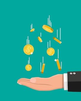 Spadające złote monety i ręka.