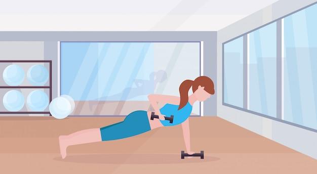 Sport kobieta robi hantle deski ćwiczenie dziewczyna podnoszenie ciężarów pracy w siłowni crossfit szkolenia zdrowego stylu życia koncepcja płaskie nowoczesny klub zdrowia studio wnętrz wnętrze poziome