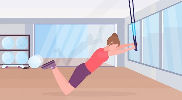Sportowa kobieta robi ćwiczenia z zawieszeniem paski fitness elastyczna lina dziewczyna trening crossfit trening koncepcja nowoczesna siłownia studio wnętrze poziomej płaskiej pełnej pełnej długości