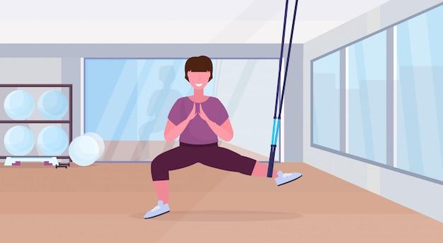 Sportowa kobieta robi przysiady ćwiczenia z zawieszeniem paski fitness elastyczna lina dziewczyna szkolenia crossfit trening koncepcja nowoczesny klub zdrowia studio wnętrze płaskie płaskie pełnej długości