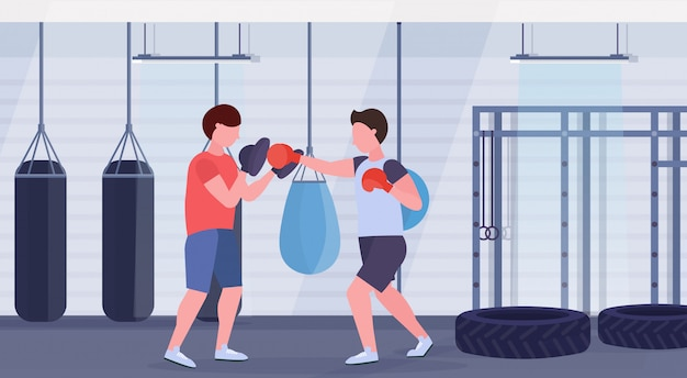 Sportowca bokser ćwiczy ćwiczenia bokserskie z męskim trenerem mężczyzna wojownik w czerwonych rękawiczkach ćwiczenia walki klub wnętrze zdrowego stylu życia koncepcja płaskie poziome