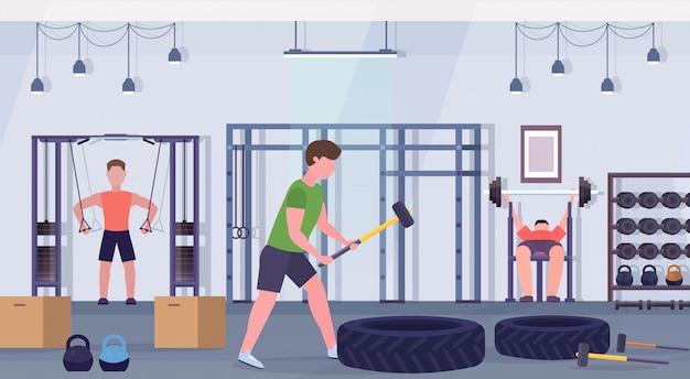 Sportowi ludzie robią ćwiczenia mężczyźni pracujący razem na aparat treningowy w siłowni crossfit trening zdrowego stylu życia koncepcja nowoczesny klub zdrowia studio wnętrze poziomej