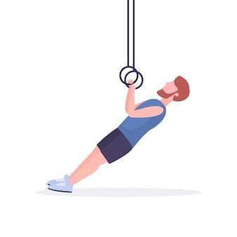Sportowy mężczyzna robi pierścień zanurza ćwiczenia z pierścieniami gimnastycznymi facet szkolenia w siłowni trening cardio crossfit zdrowy styl życia koncepcja białe tło pełnej długości