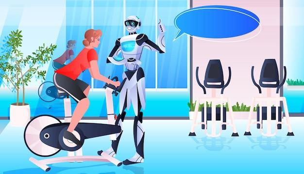 Sportsmenka jeździ na rowerze stacjonarnym z instruktorem robota trenuje zdrowy styl życia technologia sztucznej inteligencji