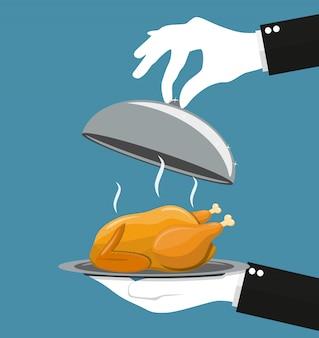 Srebrny klosz podający pieczonego kurczaka na talerzu.