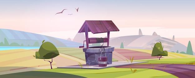 Stara kamienna studnia z wodą pitną na zielonym wzgórzu z polami uprawnymi
