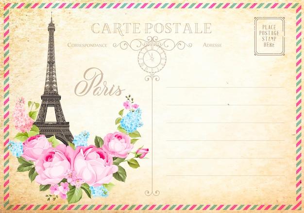 Stara pusta pocztówka ze znaczkami pocztowymi i wieżą eiffla z wiosennymi kwiatami na górze.