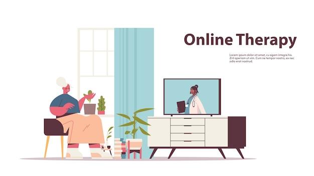 Starsza kobieta ogląda online konsultacje wideo z lekarzem kobietą na ekranie telewizora opieka zdrowotna telemedycyna porady medyczne kopia przestrzeń