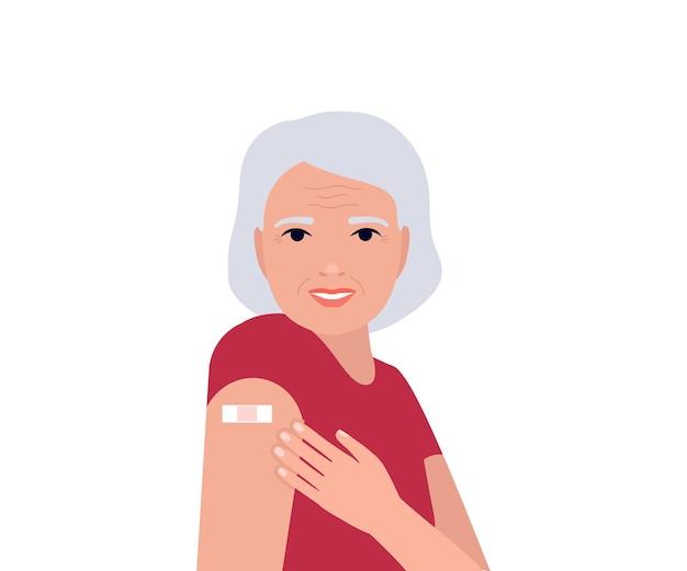 Starsza kobieta po szczepieniu pokazuje rękę z łatą ręką z bandażem koncepcja szczepionki na koronawirusa
