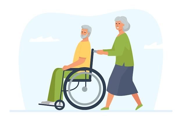 Starsza kobieta przewraca swojego niepełnosprawnego męża na wózku inwalidzkim. spacer i rozrywka dojrzałej pary.