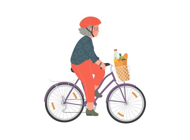 Starsza kobieta w kasku jeździ na rowerze z torbą na zakupy na rowerze