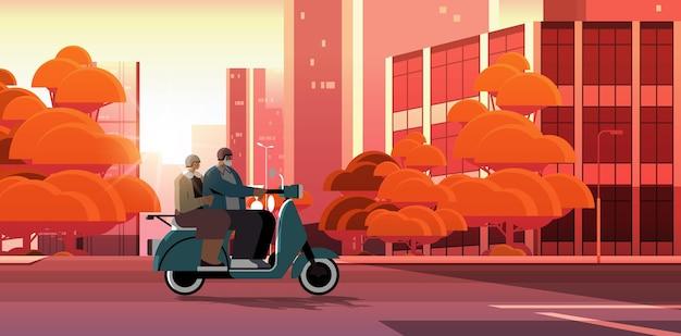 Starsza para w kaskach jazdy skuterem na ulicy miasta dziadkowie podróżujący na motorowerze aktywnej koncepcji starości