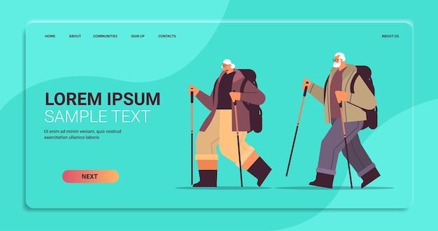 Starszy kobieta mężczyzna wędrowcy podróżujący z plecakami i kijami na spacer nordic walking aktywna koncepcja starości