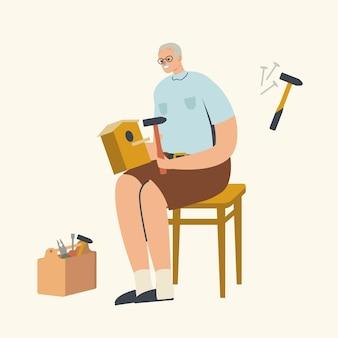 Starszy męski charakter dokonywanie birdhouse. dziadek siedzący na stołku robi dom dla ptaków przy użyciu instrumentów stolarskich