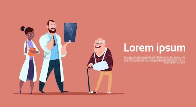 Starszy mężczyzna na konsultacje z grupą lekarzy, emeryt lub rencista w koncepcji opieki zdrowotnej szpitala