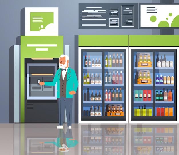 Starszy mężczyzna trzyma kartę kredytową za pomocą bankomatu