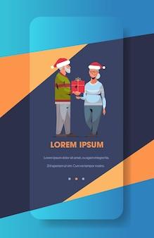 Starszy mężczyzna w czapce mikołaja wręczający prezent pudełko dojrzałej kobiecie rodzina świętuje wesołych świąt szczęśliwego nowego roku ferie zimowe koncepcja ekran smartfona aplikacja mobilna online w pionie