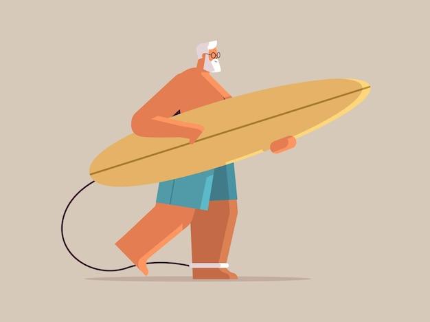 Starszy mężczyzna z deską surfingową w wieku męskim surferem trzymającym deskę surfingową letnie wakacje aktywna koncepcja starości