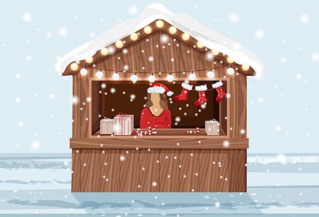 Stoisko świąteczne z kobietą w kapeluszu sprzedaży produktów wakacyjnych