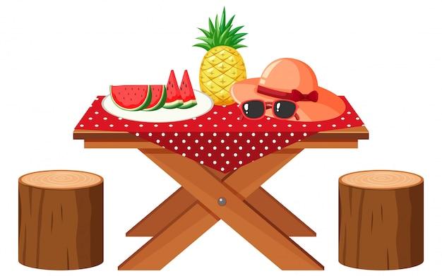 Stół piknikowy ze świeżymi owocami i kapelusz na białym tle