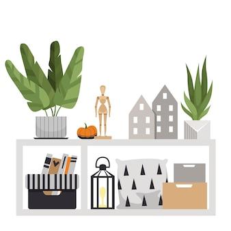 Stół podłogowy z elementami wyposażenia wnętrz. roślina, poduszki, pudełka, drewniana figurka, dynia, domki i latarka. kompozycja wnętrz w stylu skandynawskim.
