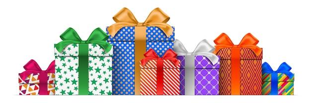 Stos pudełek prezentowych o różnej wysokości, z kolorowymi wzorami pakowania, stojący na białym tle na białym tle.