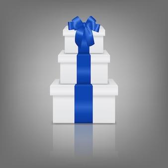 Stos trzech realistycznych białych pudełek prezentowych z niebieską wstążką i kokardką