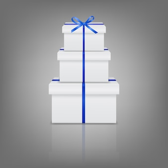Stos trzech realistycznych białych pudełek z niebieską wstążką i kokardą