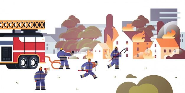 Strażacy w pobliżu straży pożarnej przygotowują się do gaszenia strażaków w mundurach i hełmach strażak koncepcja pogotowia płonące domy pejzaż