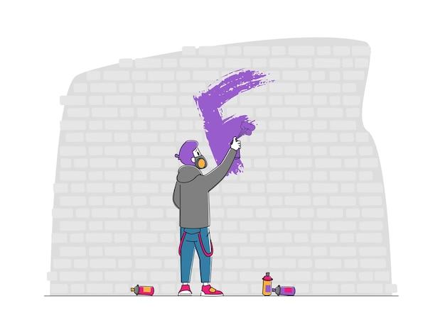 Street artist nastolatek w respirator maluje graffiti na ścianie