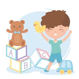Strefa dla dzieci, śliczny mały chłopiec alfabet blokuje misia i zabawki samochodowe