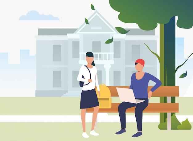 Studenci studiujący i rozmawiający w parku kampusowym