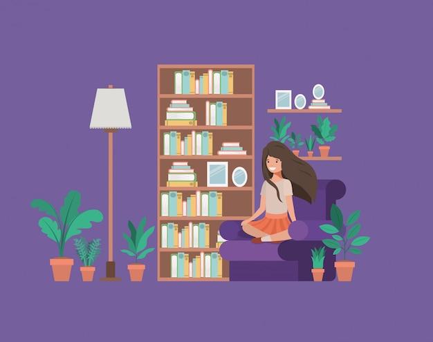 Studencka dziewczyna siedzi czytelniczą książkę w pokoju dziennym