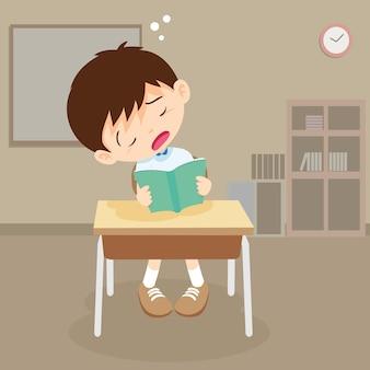 Student chłopiec czyta książkę, ale śpi w klasie
