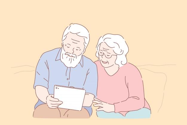 Studiowanie komputera przez osoby starsze. rozprzestrzenianie się technologii, edukacja oldstera, aktywne życie towarzyskie, komunikacja online, starsza para z tabletem, nauka korzystania z komputera razem. proste mieszkanie